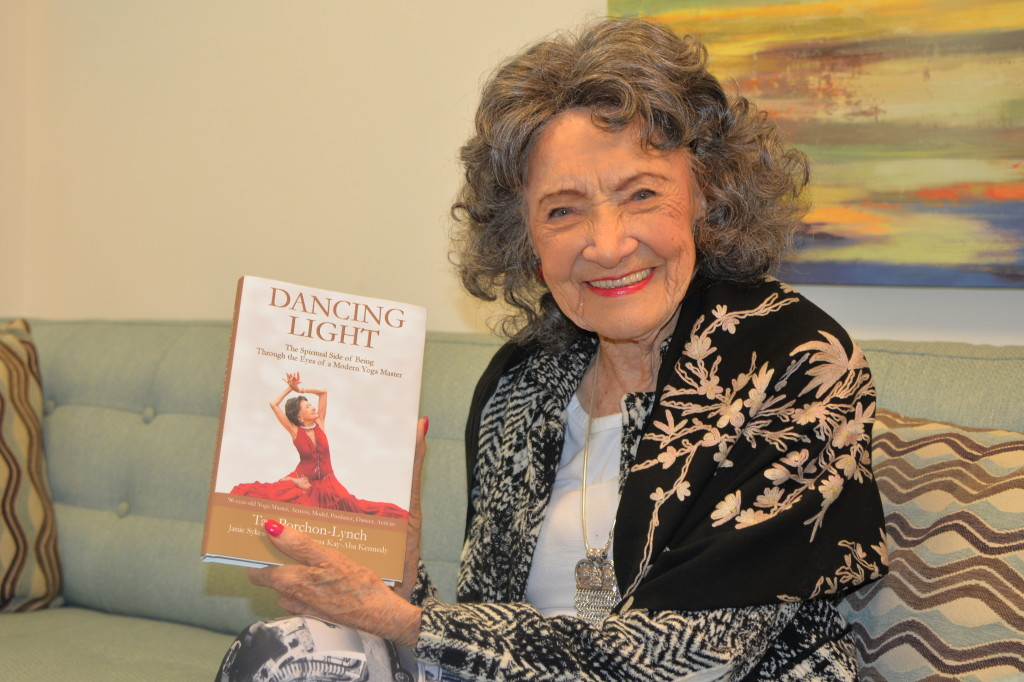 96-year-old yoga master Tao Porchon-Lynch holding her new book, Dancing Light, at the Steve Harvey Show green room in Chicago