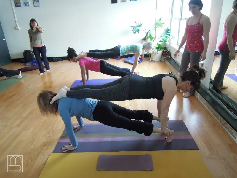 Teresa Kay-Aba Kennedy in a Stacked Plank during an AcroYoga Class
